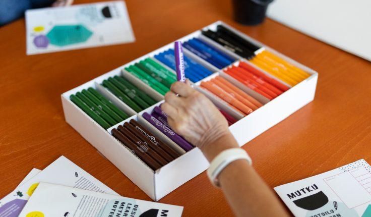 Käsi ottaa laatikosta värin.